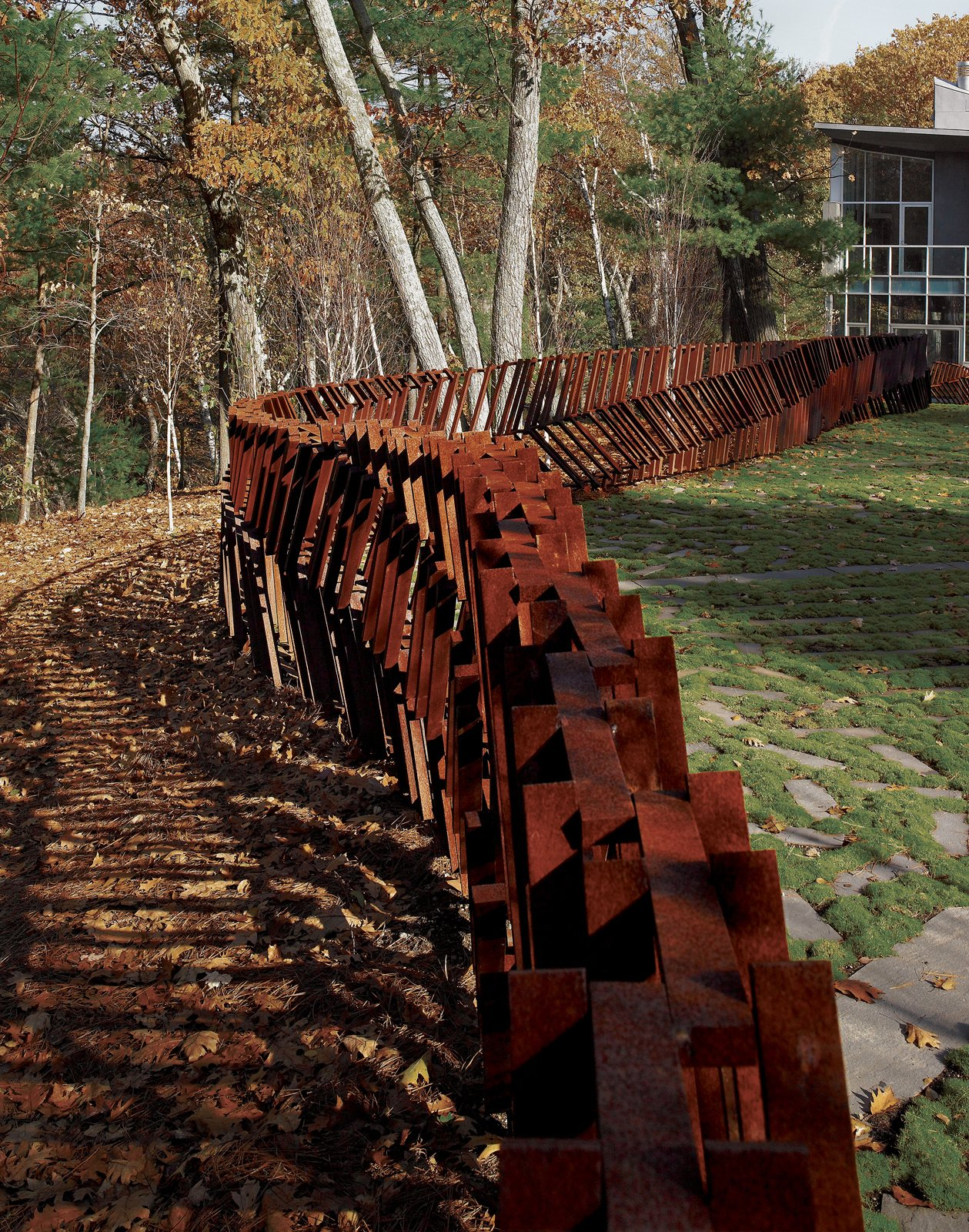 """Outdoor, Metal Fences, Wall, and Hardscapes Landscape architect and artist Mikyoung Kim created a Cor-ten steel fence to enclose a three-acre site in Lincoln, Massachusetts. """"The entire fence is made using just seven lengths of modular, precut Cor-Ten steel bars, with widths being anywhere from two to five bars thick,"""" explains the designer. """"Depending on the angle from which you see it, the fence can appear transparent or opaque."""" Read the full article here.  Photo 3 of 3 in On the Fence"""