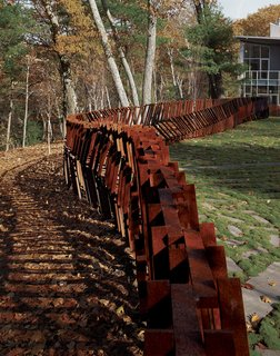 "Landscape architect and artist Mikyoung Kim created a Cor-ten steel fence to enclose a three-acre site in Lincoln, Massachusetts. ""The entire fence is made using just seven lengths of modular, precut Cor-Ten steel bars, with widths being anywhere from two to five bars thick,"" explains the designer. ""Depending on the angle from which you see it, the fence can appear transparent or opaque."""