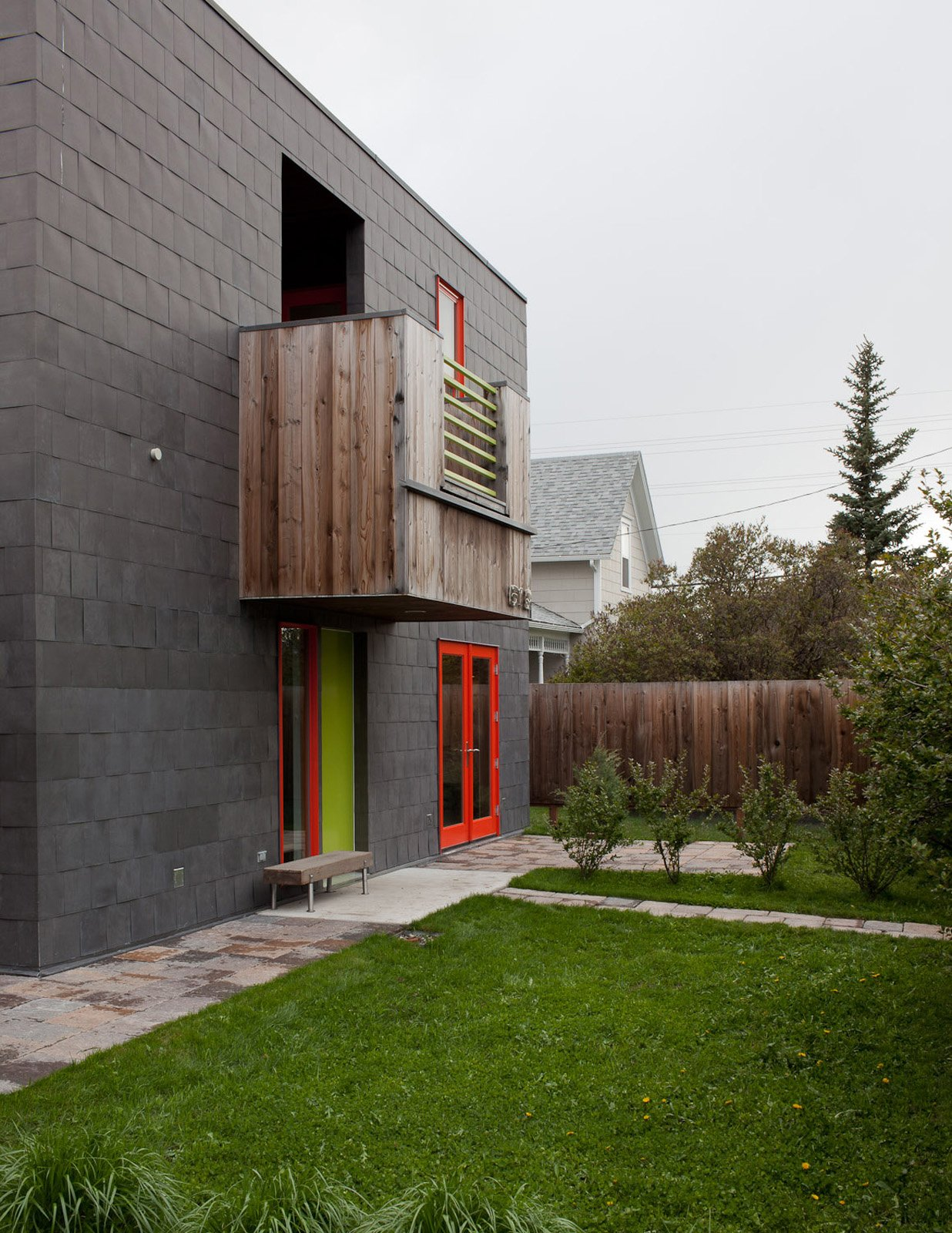 Exterior and House Building Type A handful of boxy protrusions on the facade give the modernist residence an additional three-dimensionality. The colorful window frames and door also give variety and depth to the gray structure.  Photo 10 of 16 in A Sound Professional Goes DIY While Building an Affordable Montana Home