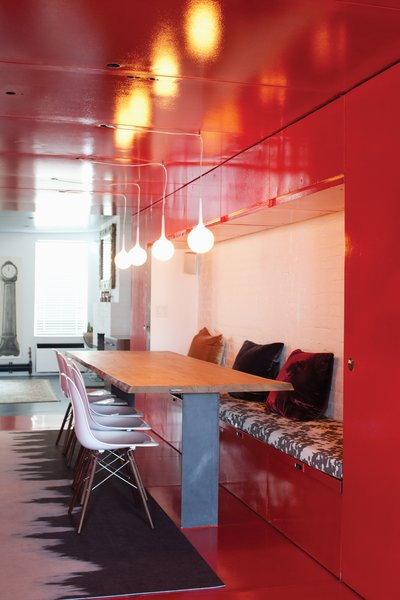Eazy side chairs by Whiteonwhite line one side of the custom-designed table by LOT-EK. Castore suspension lights by Michele De Lucchi for Artemide hang above, and a custom rug by Liora Manné lies below.  Photo 5 of 21 in Red, Red, and More Red! 20 Bold Interiors That Make a Statement