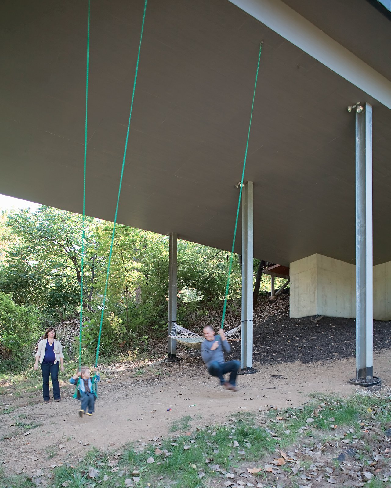 Outdoor Julie, James, and Christian enjoy an unexpected bonus of living in a house on stilts—–a pair of swings suspended from the base of the structure. The family often goes for walks on the property, looking for wildlife and playing in the tepee they built in a secluded space in the woods.  Photo 3 of 10 in 11 Hillside Homes That Feature a Balancing Act With Nature from A Lot to Love