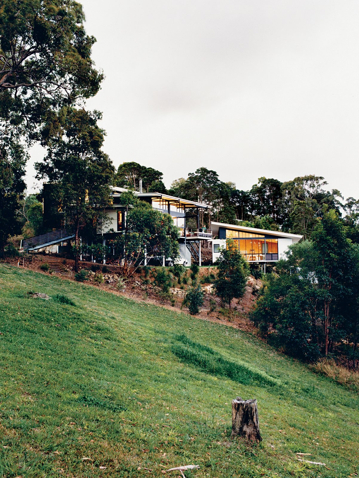 Exterior and House Building Type The Tinbeerwah house and studio keep a low profile among the site's eucalyptus trees.  Photo 1 of 12 in Hillside Family Home in Australia