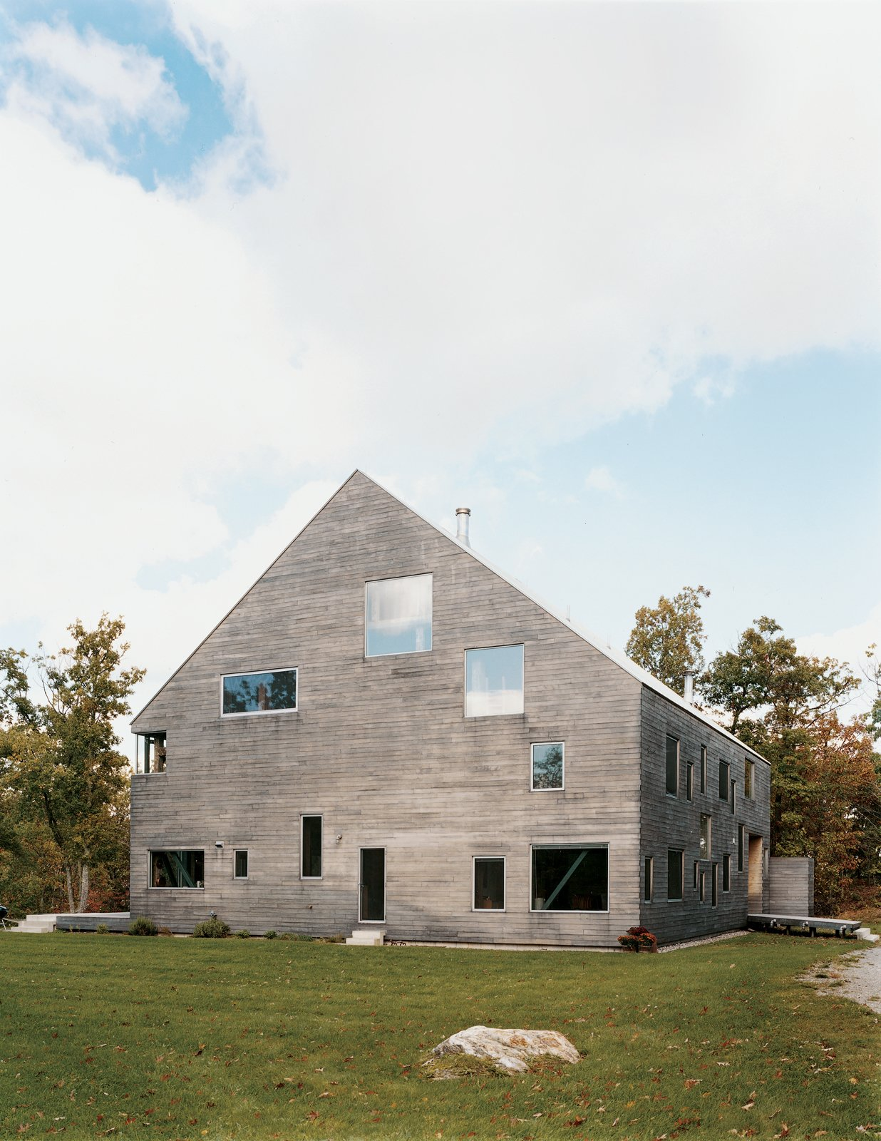 """Exterior, Barn Building Type, and Wood Siding Material The Pine Plains, New York, home of Elise and Arnold Goodman boasts 48 windows, the largest of which measures 8'6'' by 7'6''. As architect Preston Scott Cohen explains, the """"free facade makes it impossible to identify how many levels there are, or even to tell the difference between a door and a window."""" From without, the windows reveal dramatic glimpses of the 18th-century barn farm and new steel structure that support the house. From within, says Elise, """"Each season, each time of day, offers a different view of the world. It's spectacular.""""  Photo 7 of 7 in Raising the Barn"""