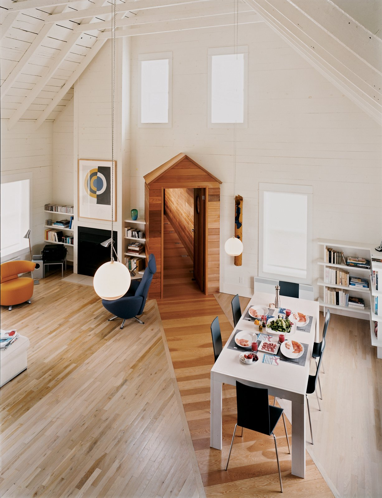 Living Room, Pendant Lighting, Chair, and Light Hardwood Floor The great room's high, pitched roof and neutral walls give the space an open, tranquil feel, making it a desirable spot for the couple to pursue two of their passions: classical music and literature.  Photo 1 of 8 in Blue in the Facade