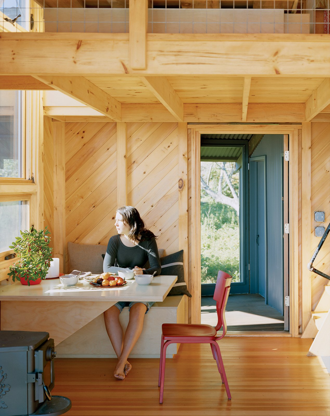 Dining Room and Table Alex enjoys a sun-filled breakfast at the built-in dining table and bench, one of many space-saving designs.  Photo 8 of 21 in A Tiny Cabin is This Writer's Off the Grid Getaway