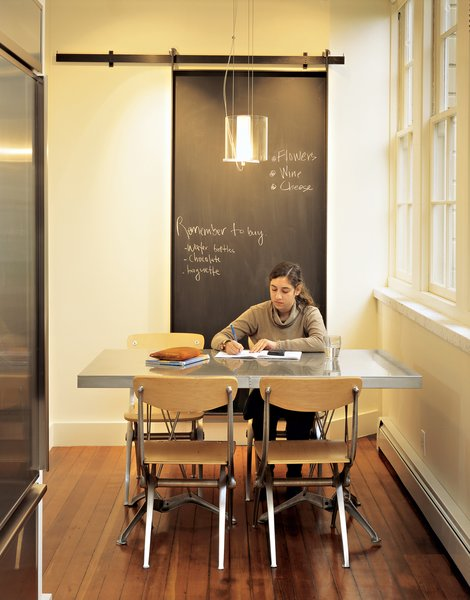 """Medium Hardwood Floor and Pendant Lighting Designer Jeff Sand's Universal Chairs combine his love for classic French café chairs with an appreciation for """"the beautiful metal casings on an old Moto Guzzi."""" Sand Studios also designed the dining table and pendant lamp.  Photo 3 of 4 in Victorian Revival"""