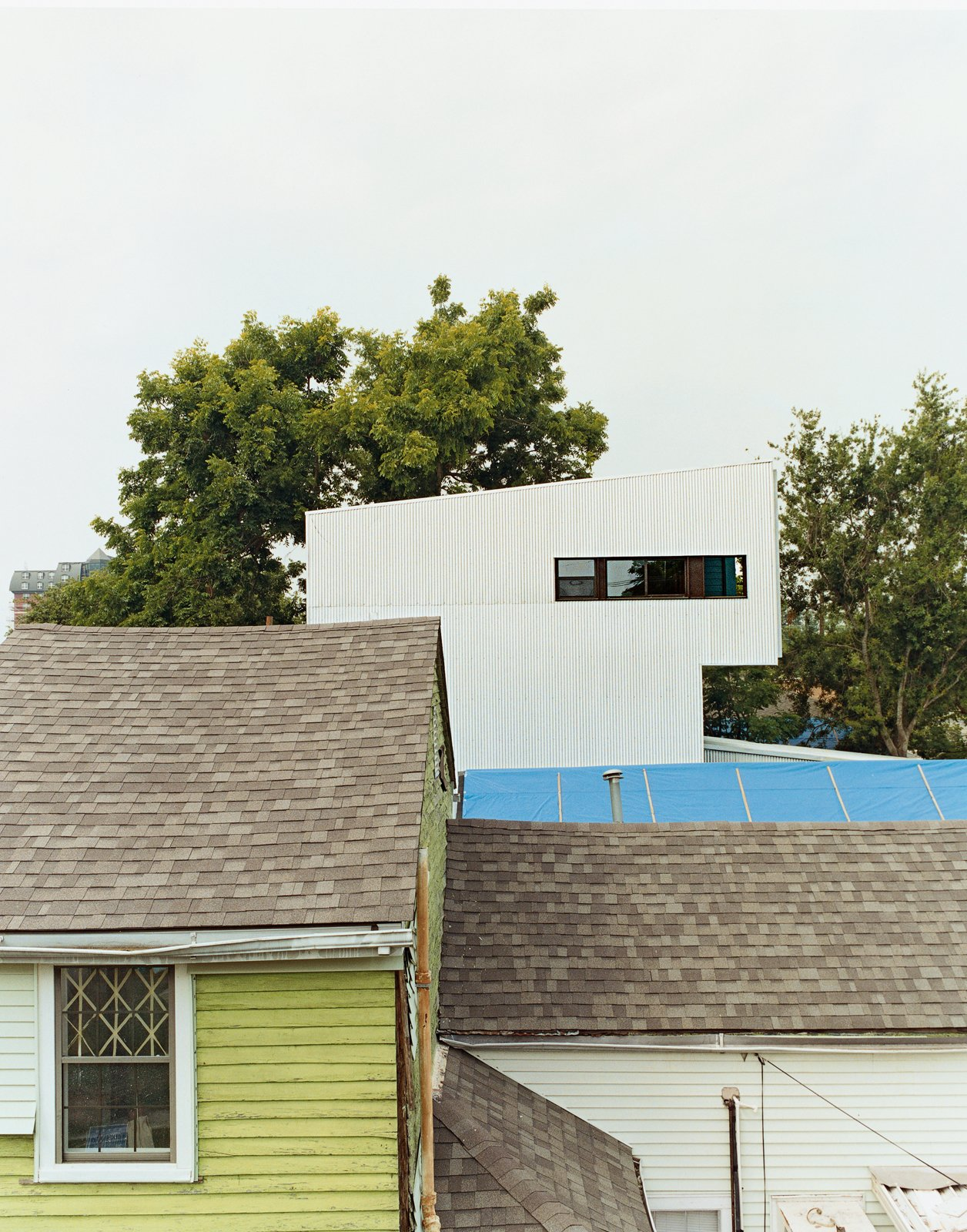 Though the Lowerline House may appear radically different, it deliberately mimics the neighboring shotgun camel-backs. The form is derived from a time when city taxes were based on the height of a building at the street front. To get more space but not get taxed, houses were built up on the rear of the property, problem solved.  Photo 8 of 11 in New Orleans, LA