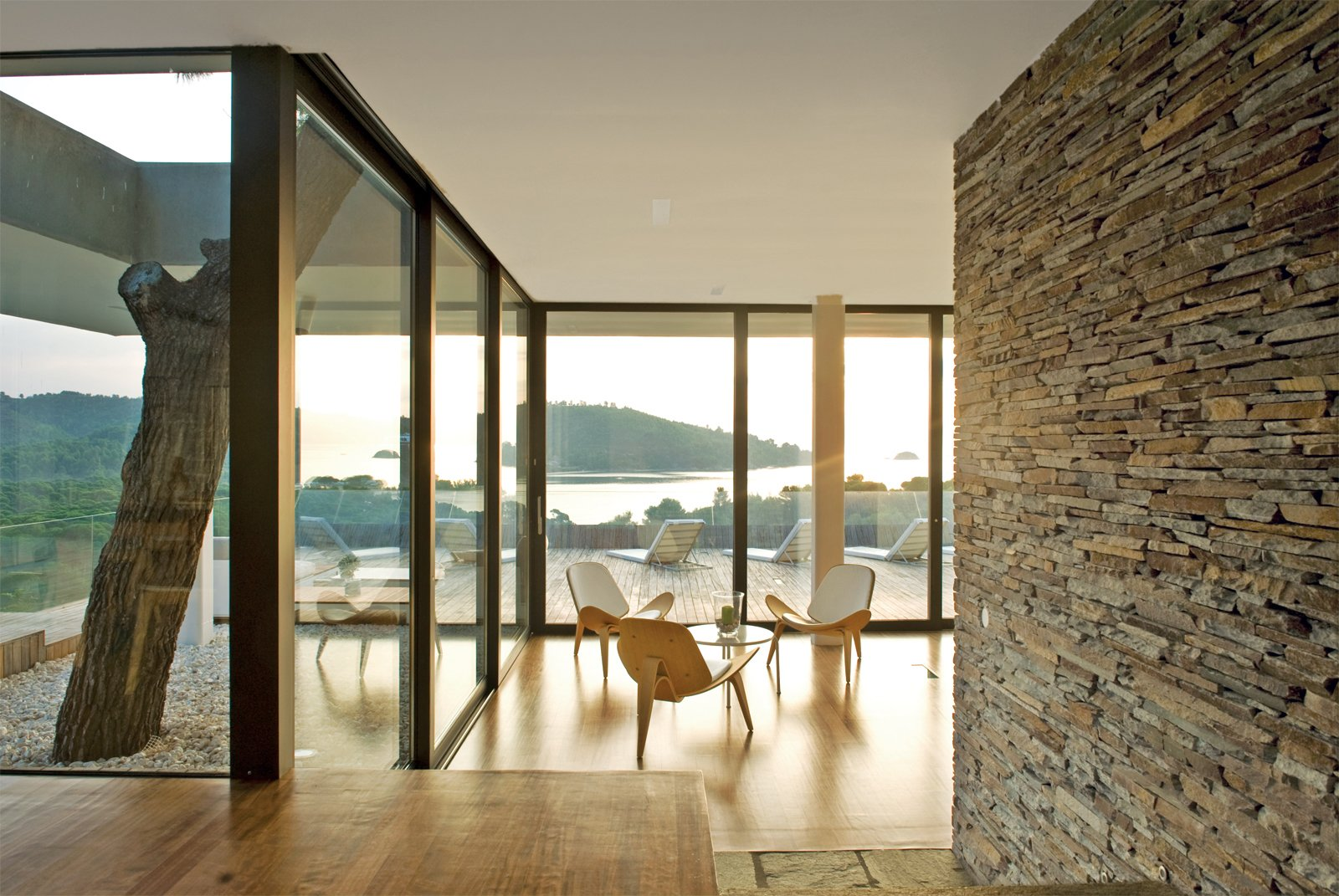 The living room, sports a trio of Shell chairs by Hans J. Wegner for Carl Hansen & Son.  Photo 11 of 13 in An Idyllic Vacation Home in Greece