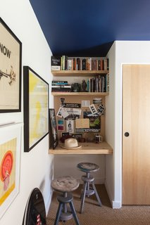 The bedroom allows for a tiny niche for a built-in wood desk. The target painting is by Alia Penner.