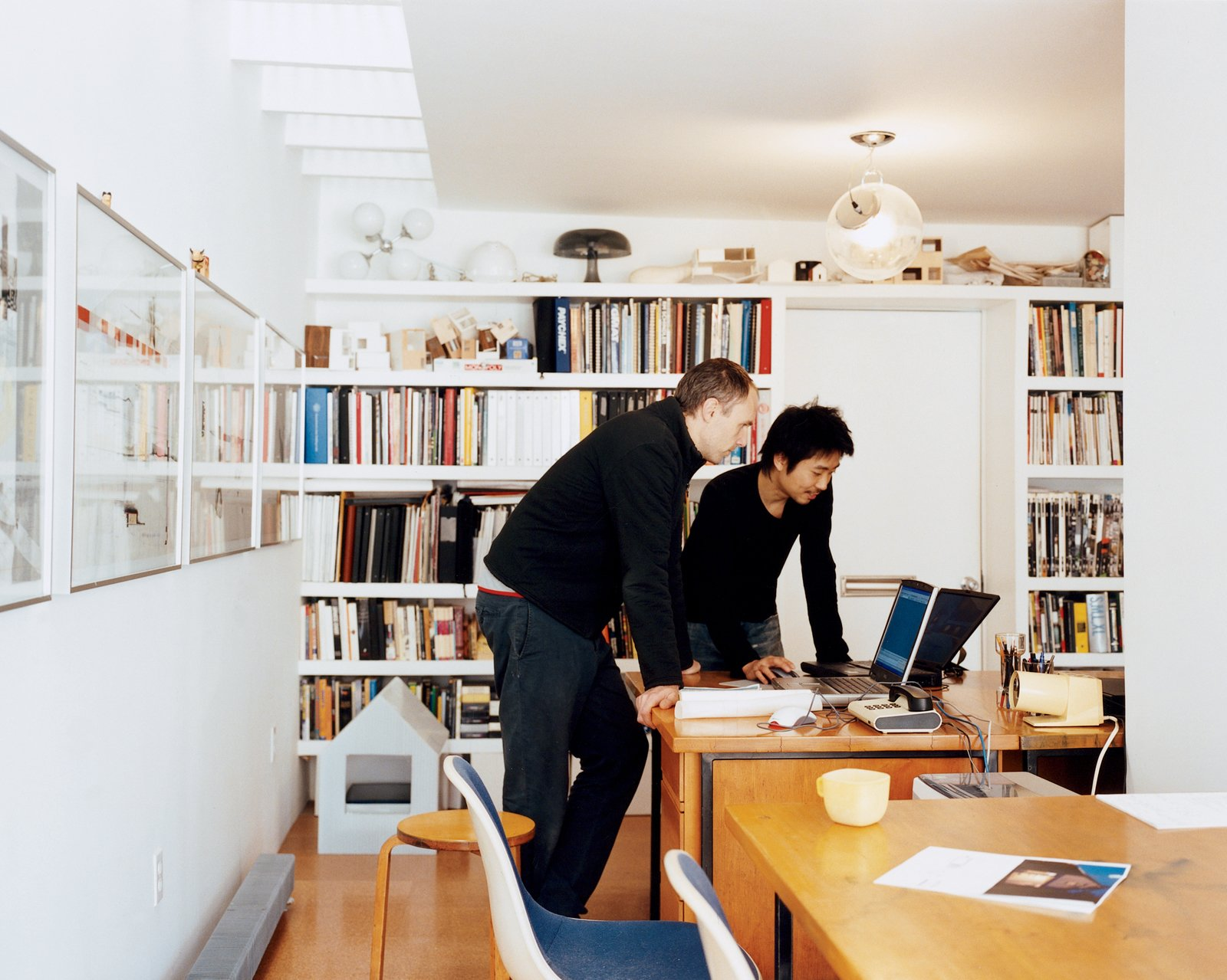 Lit by the skylight and an Artemide ceiling lamp, Schenk and Ngai consult laptops on mid-century Heywood Wakefield desks, which Fernandez salvaged from a Harvard junkyard and then restored.  Photo 8 of 11 in New Beginnings