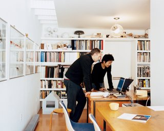 Lit by the skylight and an Artemide ceiling lamp, Schenk and Ngai consult laptops on mid-century Heywood Wakefield desks, which Fernandez salvaged from a Harvard junkyard and then restored.