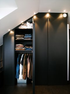 The apartment's built-in closets are deep and have mirrors on one side. Spotlights set flush overhead provide light and also allow the maximum amount of storage, all the way to the ceiling.