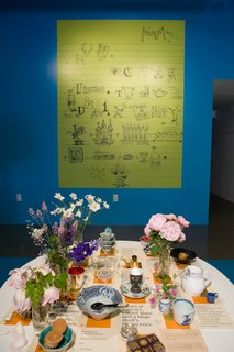 "Charles created this rebus for his daughter, Lucia, when she was a child. ""Some people want a key for it; some don't,"" says Sussman. Ray's table was curated by artist Tina Beebe, who worked closely with Ray in the Eames Office and decorated the surface with the flowers and objects Ray favored."
