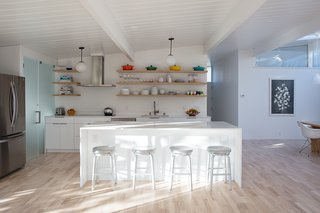 The updated kitchen features a bright white palette. The countertop is Caesarstone's Blizzard surface and the stools are Crate and Barrel. The range hood is Futuro, the refrigerator is LG, and the dishwasher is Bosch.