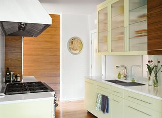 Dan Pacek and John Roynon expanded and renovated their tiny kitchen, integrating it more sensibly into their 1911 house, while borrowing natural light from secondary sources, such as a window on the landing leading to the second floor. The couple peeled away wallpaper to reveal layers of old paint that serendipitously complemented the color scheme of their new kitchen, and used a circular frame to preserve a section of it.