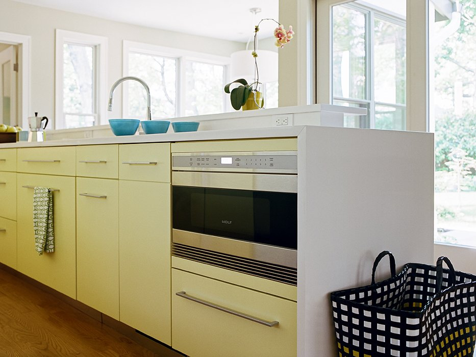 Kitchen and Colorful Cabinet In northern New Jersey, a cramped kitchen is reborn as a welcoming space for cooking and entertaining. Decked out in a subtle yellow, the kitchen houses a Wolf drawer microwave tucked unobtrusively under the counter in the display island.  Photo 7 of 25 in 25 Bold Ways to Decorate with Yellow from Cramped Kitchen Transformed Into an Inviting Hub