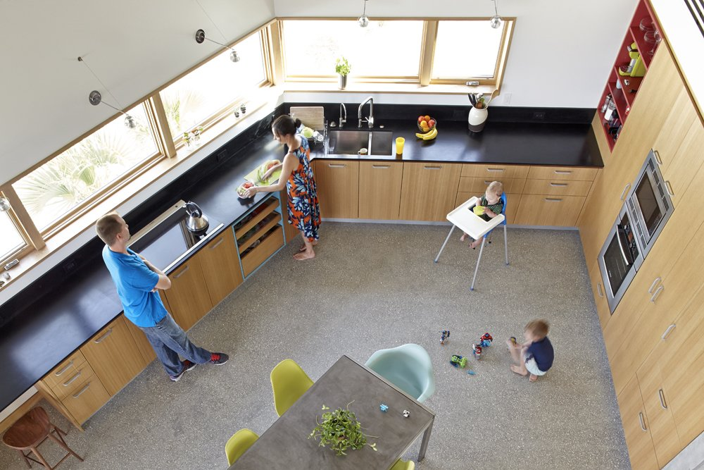The kitchen from above, looking down from the second floor. Jody Beck with hudband Ross-Alan Tisdale, partners in Traction Architecture, with their kids Robin and Jonah.  Photo 6 of 10 in Angular Modern Beach House in Florida