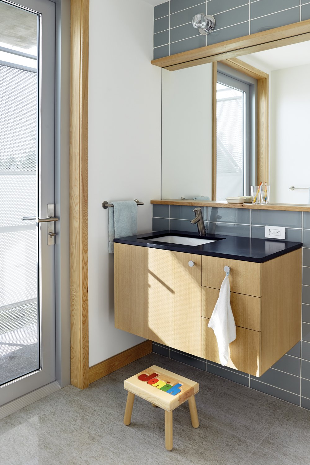 Small surprises were incorporated into the bathroom design, like a cantilevered exterior shower. Traction chose inexpensive glass subway tile and porcelain floor tile, in addition to modular cabinetry by Viola Park with Paperstone countertops.  Photo 9 of 10 in Angular Modern Beach House in Florida