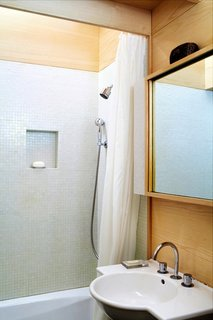 Tips for Tiny Bathrooms - Photo 1 of 12 - Faced with the challenge of a 240-square-foot New York apartment in desperate need of a refresh, architect Tim Seggerman went straight to his toolbox to craft a Nakashima-inspired interior. The architect brightens the limited space with warm wood and tiny tile. Photo by David Engelhardt.