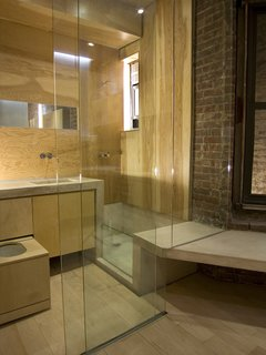 Chan outfitted the bathroom in marine fir plywood from Rosenzweig Lumber for its resistance to high-moisture environments. The fixtures are from Vola; the bathtub, countertop and sinks are of magnesite. The full-height glass is stationary except for a sliding door at left, and a curtain can be rolled down for privacy.