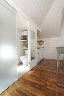 Tips for Tiny Bathrooms - Photo 11 of 12 - Azevedo shoehorned a small bathroom next to the kitchen, under the dormer. The etched translucent glass lets light into the main living area and serves as one side of the shower. Photo by Susanne Friedrich.