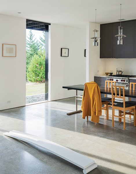 Concrete Floor Lanterns from Stelton hang above the dining table and chairs Brothers designed. Nevamar laminate covers the kitchen cabinets, which feature pulls from Häfele. The range is by Wolf.  Photo 4 of 18 in Idyllic Home Designed for an Artist
