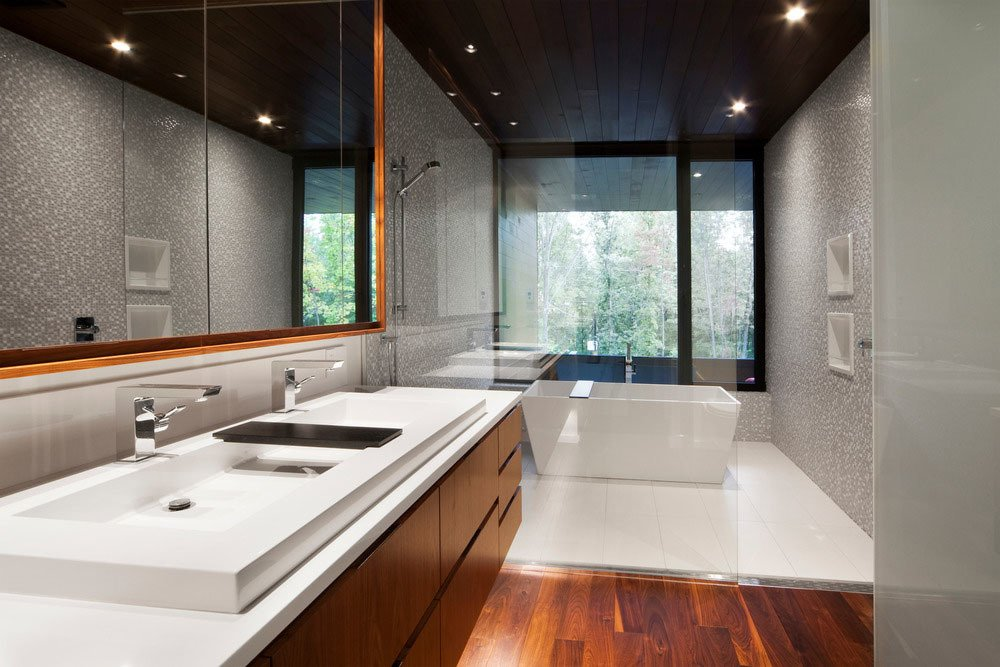 The master bedroom features an en-suite bathroom with transparent partitions.  Photo 5 of 7 in Near Montreal, a House Connects With Its Surroundings