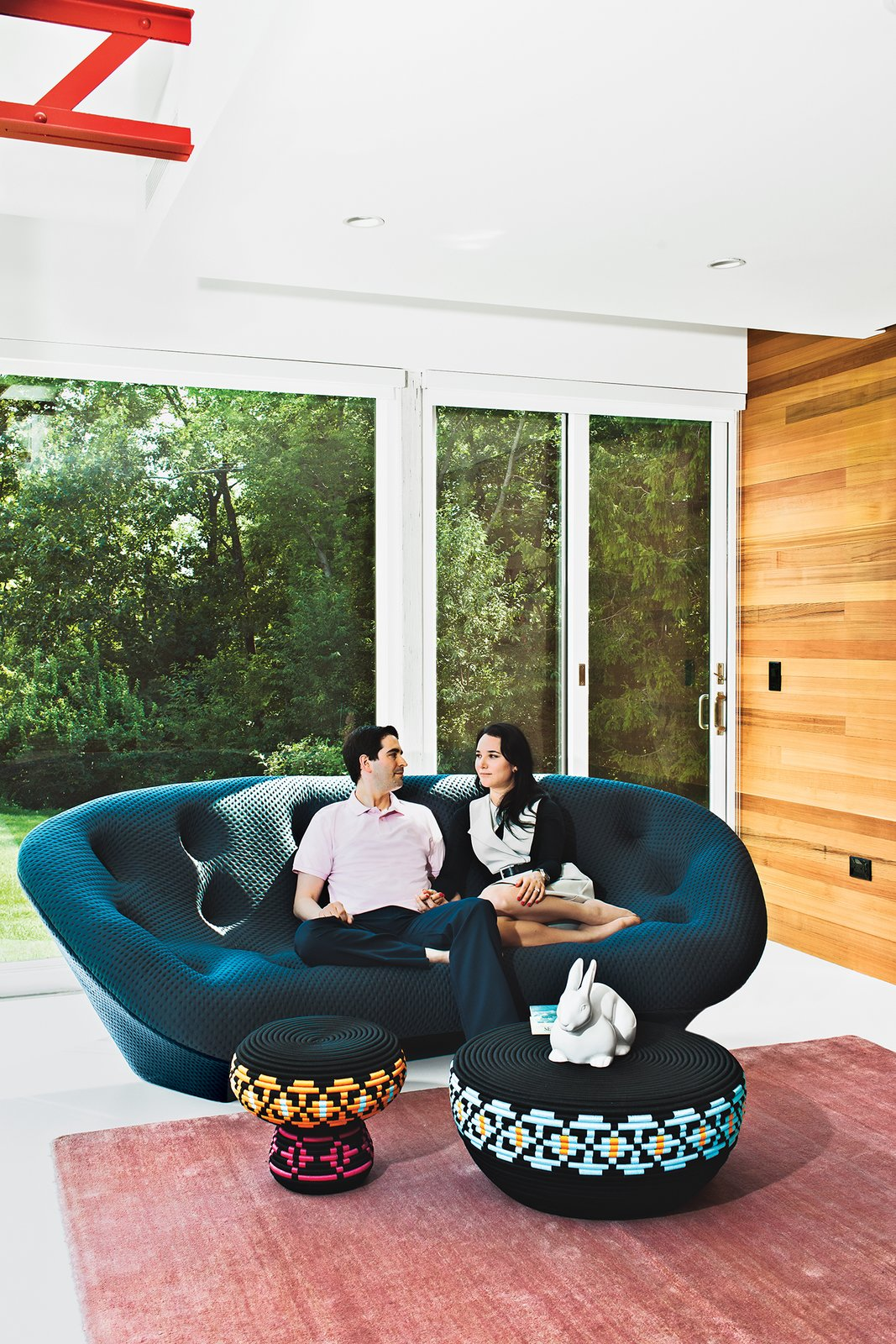 """Living Room, Sofa, Stools, and Rug Floor Steven and Tata relax in their living room. """"The house has always been deemed the 'great escape,'"""" says Steven. """"It's a very special place for us."""" The Superheroes stool and table are by Swedish designers Glimpt Studio for Cappellini, the blush-colored rug is from ABC Carpet & Home, and the Pan Pan rabbit figurine is by Ligne Roset.  Photo 12 of 12 in The Midcentury Spirit is Alive and Well in This Hudson Valley Escape"""