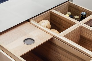 The residents store perishable items that don't need refrigeration—like fruits, vegetables, onions, and garlic—in maple-lined pantry drawers.