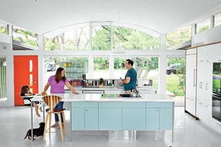 "A 1960s home with an unusual awning gets upgraded with 21st-century conveniences, all while maintaining its Austin street cred. Though the kitchen fits in with its period surroundings, a few tweaks keep it current. ""It's functional in a way that doesn't feel like the kitchen is in the living room,"" says architect Rick Black. He explains, ""one of the goals was to make the islands more like furniture and less like heavy objects that go all the way to the floor."""
