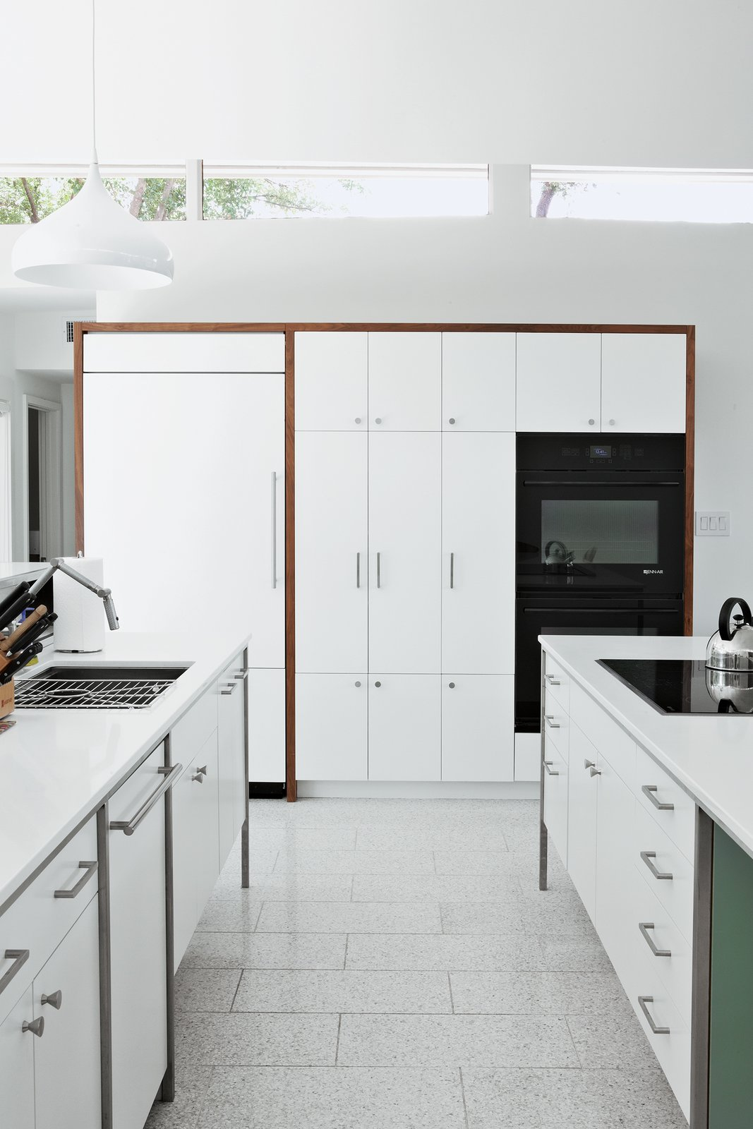 Kitchen, White Cabinet, Undermount Sink, Wall Oven, Pendant Lighting, Cooktops, Refrigerator, and Dishwasher The cooktop, refrigerator, and wall ovens are by Jenn-Air; the sink and faucet are by Kohler; and the countertops are from Caesarstone.    Photo 3 of 11 in A Renovated Midcentury Gem in Austin
