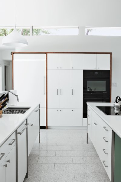 The cooktop, refrigerator, and wall ovens are by Jenn-Air; the sink and faucet are by Kohler; and the countertops are from Caesarstone.