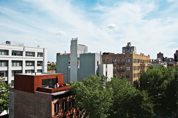 Alex Gil and Claudia DeSimio created a duplex in an apartment building where they'd been renting for years in Brooklyn, New York, and set to work gutting the interior and adding a new rooftop addition clad in panels of Cor-Ten steel.