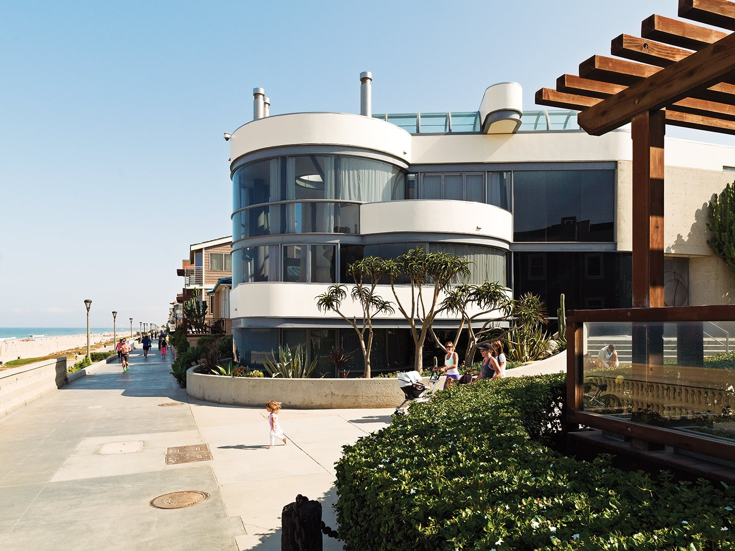The glass-walled facade faces the Strand.  Photo 3 of 11 in A Renovated Ray Kappe Abode in Manhattan Beach