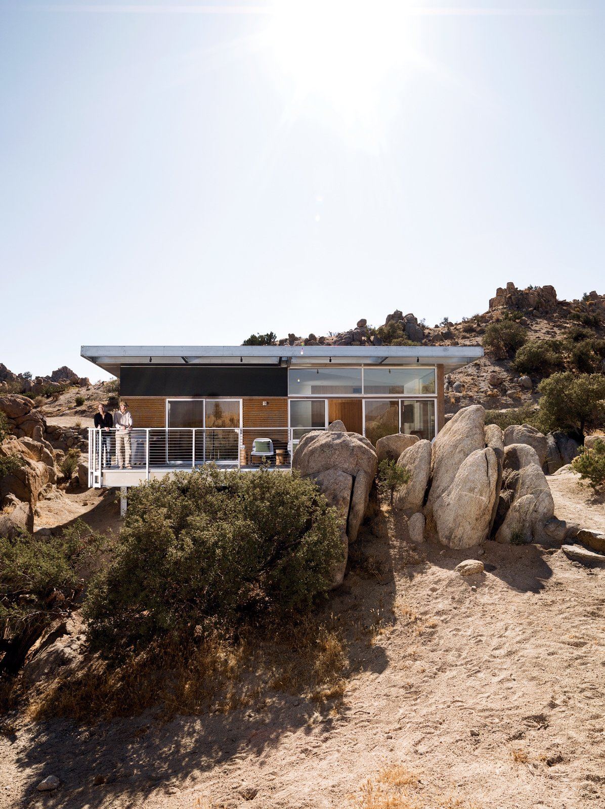 """Outdoor, Boulders, Trees, Small Patio, Porch, Deck, Back Yard, Wood Patio, Porch, Deck, Metal Patio, Porch, Deck, and Desert The Blue Sky prototype house leads a second life as desert getaway for David McAdam and his partner Scott Smith.  Photo 1 of 10 in Small """"Hybrid Prefab"""" Home in the Desert"""