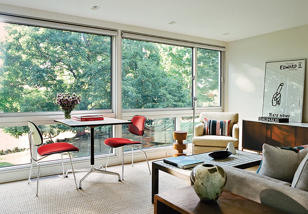 Living Room, Chair, Sofa, and Rug Floor A Universal Base Table and a pair of upholstered Molded Plywood Dining Chairs, all by Charles and Ray Eames for Herman Miller, are positioned by the window.  Photo 2 of 5 in These 5 Transformations Show Why Challenging Renovations Are Worth It