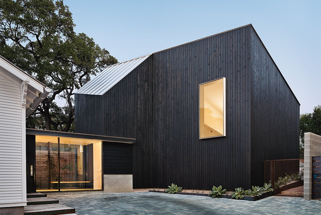 Exterior, Wood Siding Material, and House Building Type The addition, which has cypress paneling and a metal roof, is united with the renovated 1920s bungalow via a glass pavilion.  Photo 3 of 5 in These 5 Transformations Show Why Challenging Renovations Are Worth It from 1920s Bungalow Plus Modern Addition Equals Perfect Austin Home