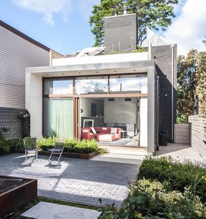 In the rear of the house, a new addition extends the living space and adds a roof terrace off the second-floor master bedroom. A garden is accessible through a wall of sliding glass doors with Sapele mahogany frames, set back to control solar gain.
