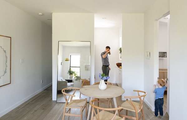 A large metal floating mirror from Restoration Hardware seemingly doubles the 675 square feet of the Schmidt-Friedlander apartment in Windsor Terrace, Brooklyn. The family of three dines at an oak table from Canvas Home, with Wishbone chairs by Hans Wegner. Decorators White paint by Benjamin Moore and oiled Hakwood European oak flooring are used throughout.