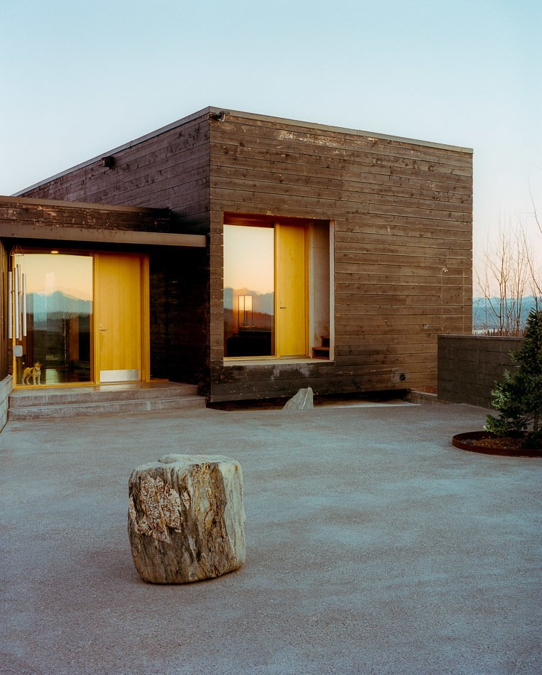 The House for a Musher is all about taking advantage of its hilltop site. The courtyard in the front has vast views and the house itself is oriented toward the surrounding landscape. Tagged: Exterior, House, Cabin Building Type, Wood Siding Material, Prefab Building Type, and Flat RoofLine.  Cabin by Matthew Nettles from This Modern Cabin Is the Ideal HQ For a Family in Alaska