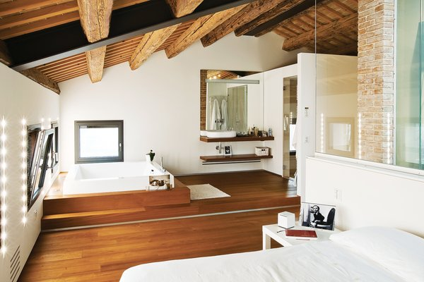 """The top floor holds the Chiavellis' bedroom suite, with a dressing room and built-in spa. """"The farmers dried their crops up here,"""" says Chiavelli. """"We knew right away this was the spot that we wanted to have our own room.""""  Photo 7 of 13 in A Renovated Farmhouse in Northern Italy"""
