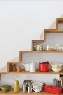 In interior designer Kathryn Tyler's home, this custom-built shelving is located under the run of a staircase, providing additional storage space to the adjacent kitchen. The wood of the shelves is seamlessly aligned with the treads of the stairs, and the back of the shelves is painted white to match the walls for a crisp look.