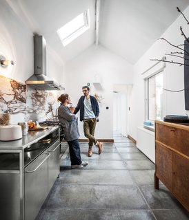 By introducing chic new elements, a Belgian couple takes a gentle approach to transforming a tired house into a vibrant workshop. Homeowners Michaël Verheyden and Saartje Vereecke were undaunted by the prospect of renovating their crumbling 1930s brick house on a tight budget. For the new kitchen, they incorporated a Smeg cooktop, oven, and range hood, stainless steel cabinets from Habitat, and personal accessories like a prototype goblet.