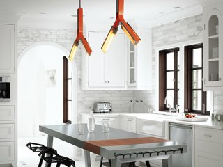 """Barbara Hill had the overhead lighting in the kitchen customized by Rich Brilliant Willing in a pert orange that accents the primarily black-and-white interior scheme. She added a stainless steel kitchen island by Bulthaup, its glossiness and """"clean feel"""" tempered by the plastic stacking stools designed by Konstantin Grcic for Magis. The cabinets, appliances, countertops, and marble tile were kept as-is, with the addition of several coats of white paint in order to blend seamlessly with the walls."""