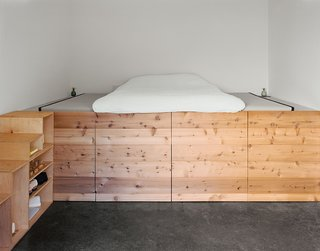 The couple's bedroom, occupying a space that was once a machine shop, has a cedar sleeping platform designed and built by Elliot Loh.