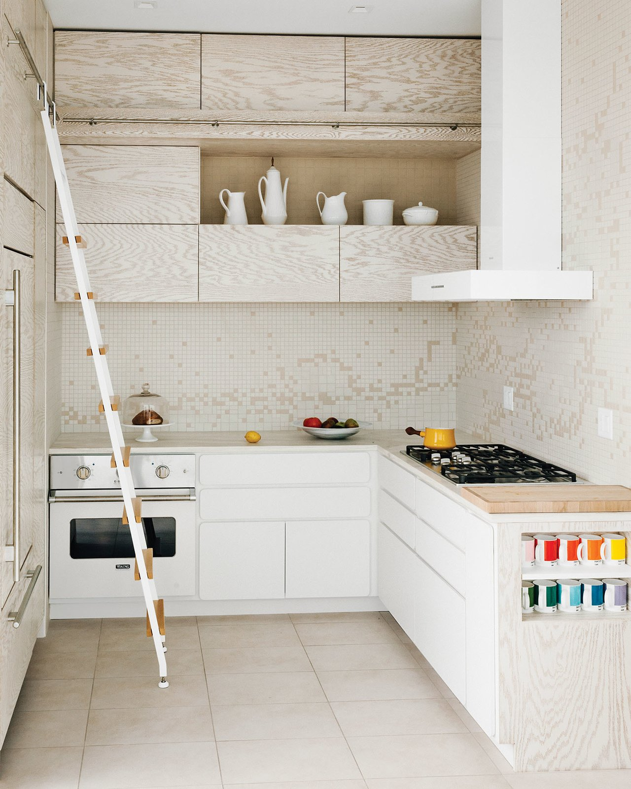 """Kitchen, Mosaic Tile Backsplashe, Range Hood, Range, Wall Oven, Recessed Lighting, Wood Counter, Refrigerator, and White Cabinet To complement the white-washed custom cabinetry in her kitchen, architect Julie Salles Schaffer has designed a tile backsplash to resemble """"melting butter in a white pan"""". Daltile arranged her two-color AutoCAD design—white and off-white—onto a mesh backing for a small fee. To soften the edges of the cabinets' drawers and doors, Schaffer requested radial edging.    Photo 2 of 6 in An Arctic White Kitchen Renovation in Connecticut"""