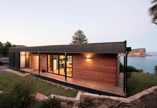 The Best Prefab Homes in Australia - Photo 3 of 10 - A prefab house designed by ArchiBlox on the northern beaches of Sydney sustains high winds and spray from the surf, so the firm wrapped the exterior in marine-grade Colorbond Ultra steel. Panels of Queensland blue gum, a native Australian hardwood, clad the street-side facade, which is protected from the harsh climate.