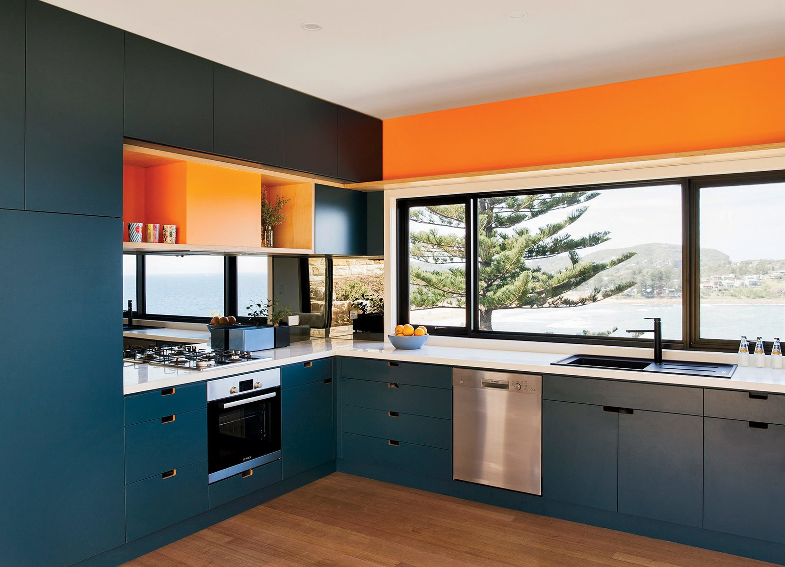 Kitchen, Dishwasher, Colorful Cabinet, Range, Drop In Sink, and Medium Hardwood Floor Inspired by the sea and sand, the couple chose blue and orange joinery colors. The oven, cooktop, range hood, and dishwasher are by Bosch.  Photo 2 of 4 in A Dramatic Cliffside Prefab Steps from the Beach in Australia