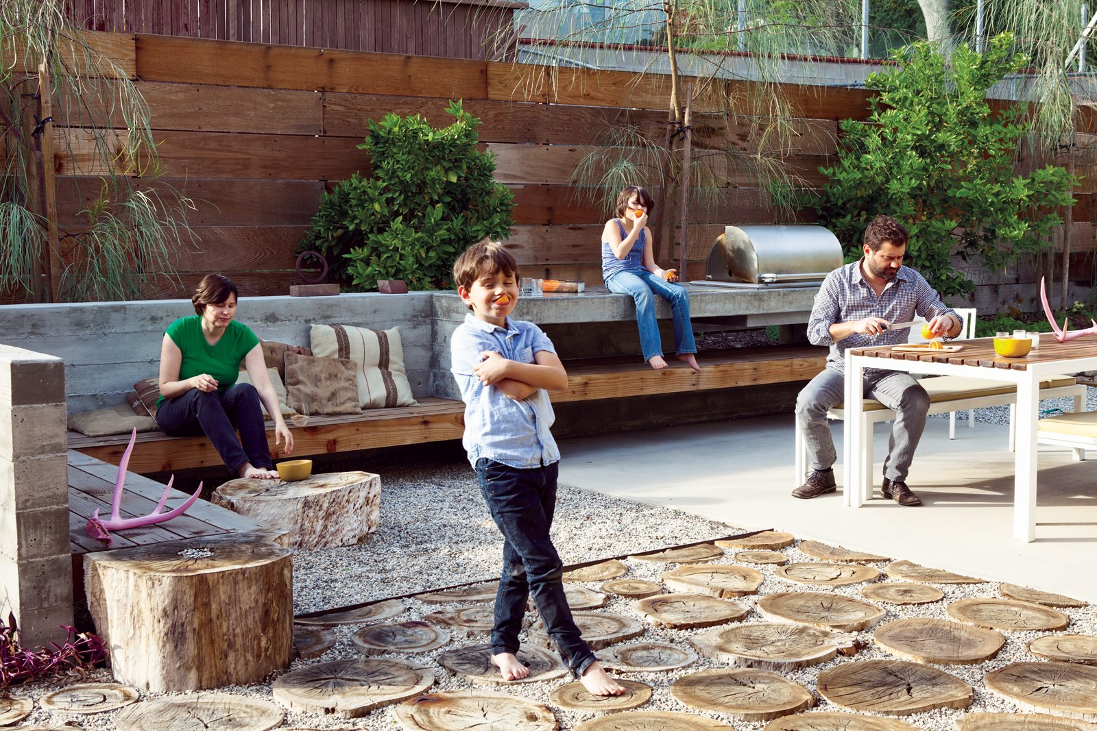 """Outdoor, Stone Patio, Porch, Deck, Concrete Patio, Porch, Deck, Horizontal Fences, Wall, and Back Yard The first thing landscape designer Laura Cooper asked Devis and Purdy was to recall childhood gardens and outdoor play. In that spirit, she designed their backyard, integrating the high ground with the low just outside the """"kids' wing."""" The resulting series of outdoor rooms on this quarter-acre is full of memory and play.  Photo 5 of 13 in A Fresh Dose of Color Livens Up This Midcentury Los Angeles Home"""