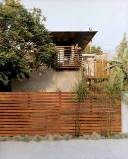 Trellis-like balcony railing cue the exposed timber frame extending over the house. The balcony and fence are made from sustainably harvested ipe wood.